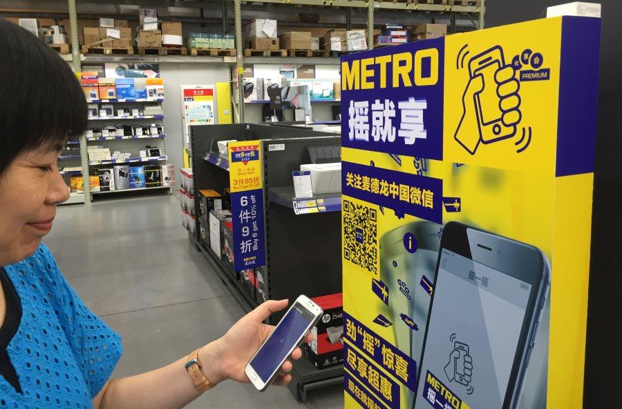vrouw demonstreert WeChat Shake-function in Metro winkel in Shanghai